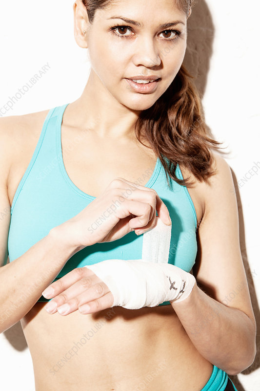 Young woman wrapping bandage on wrist