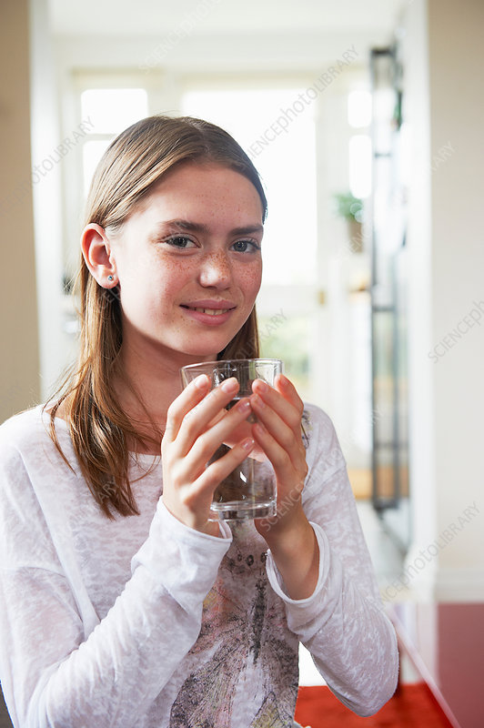 Teenage girl holding glass of water