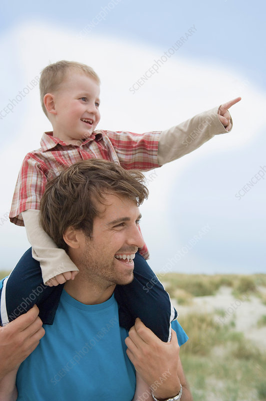 Boy on father's shoulders, pointing