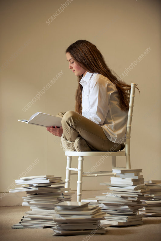 Girl sitting on chair reading book