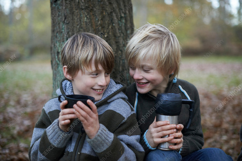 Boys drinking hot drinks in forest