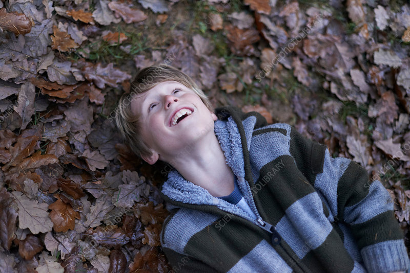 Boy lying on back on forest floor
