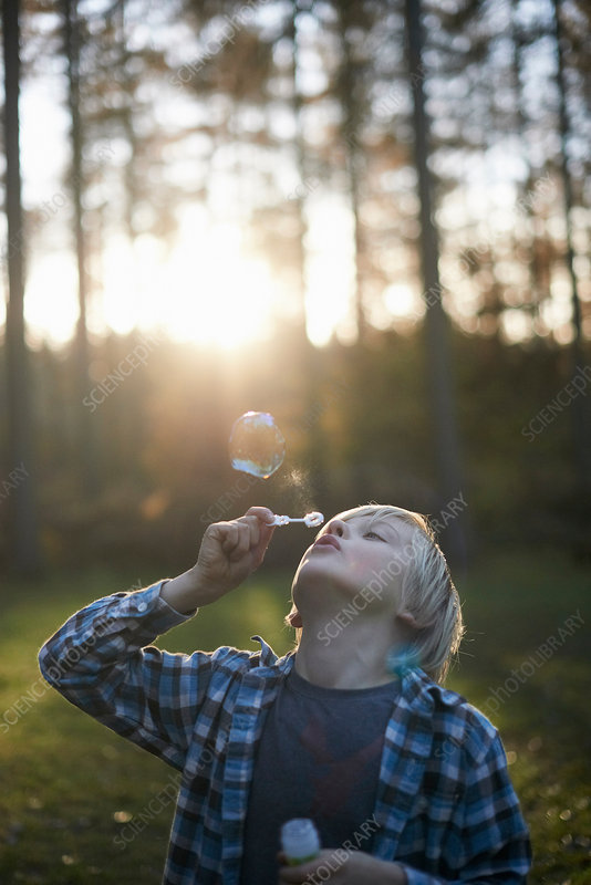 Boy blowing bubbles in forest
