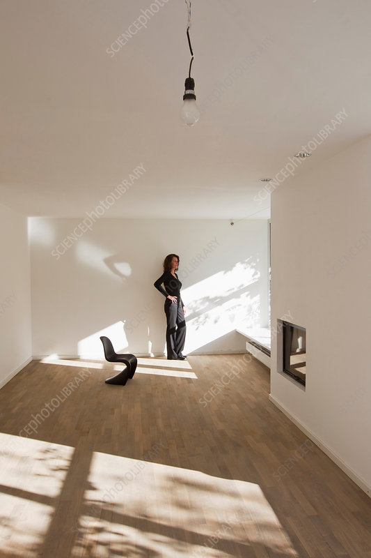 Woman standing by wall in empty room