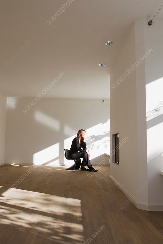 Woman sitting on chair in empty room