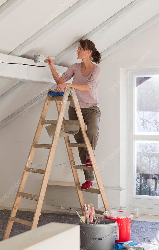 Woman on stepladder painting ceiling