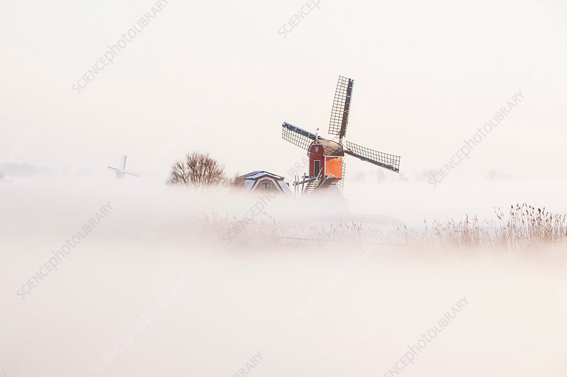 Old fashioned windmill in misty landscape