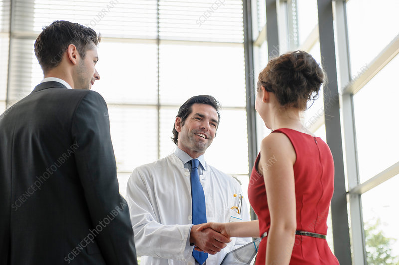 Doctor shaking hands with young couple
