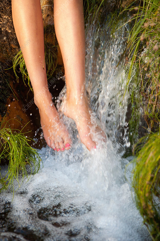 Young woman bathing feet under waterfall