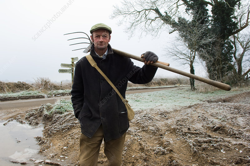 Mature farmer holding pitchfork