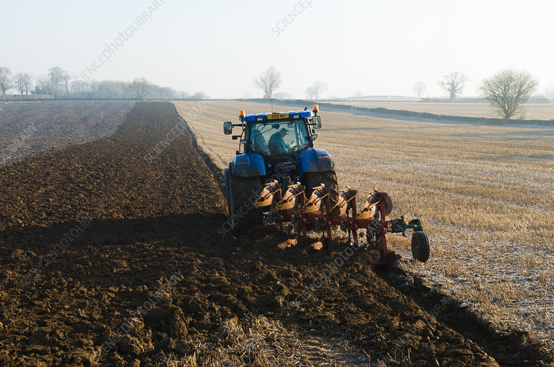 Tractor ploughing the ground of field