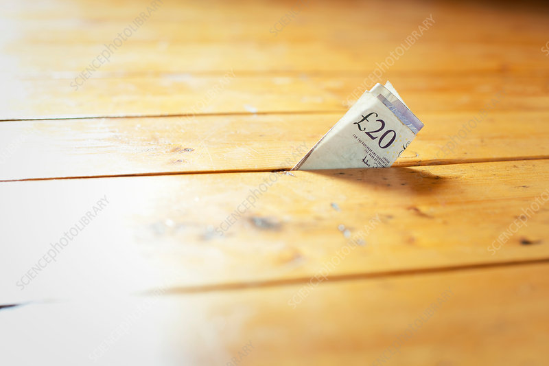 Twenty pound note in between floorboards