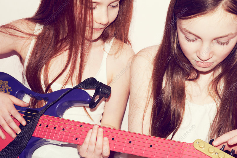 Two girls playing guitar in bedroom