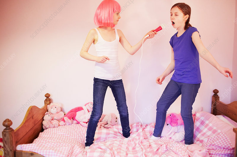 Two girls standing on bed singing