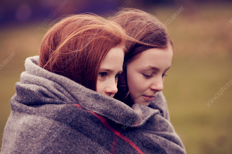 Girls wrapped in a blanket outdoors