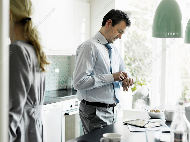 Businessman checking time in kitchen