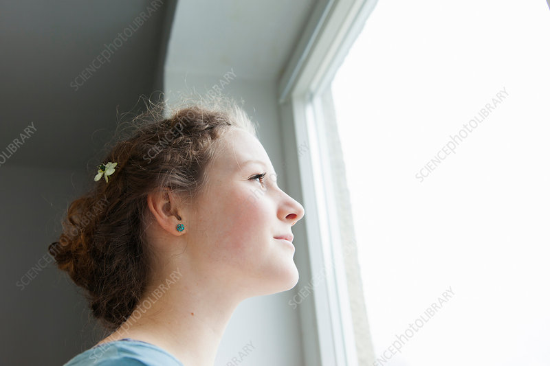 Teenage girl looking out of window