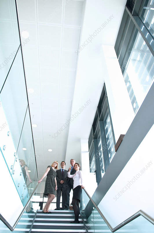 Colleagues standing on staircase