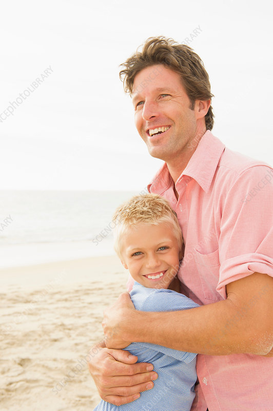Father and son hugging on beach