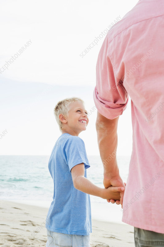 Father and son holding hands on beach