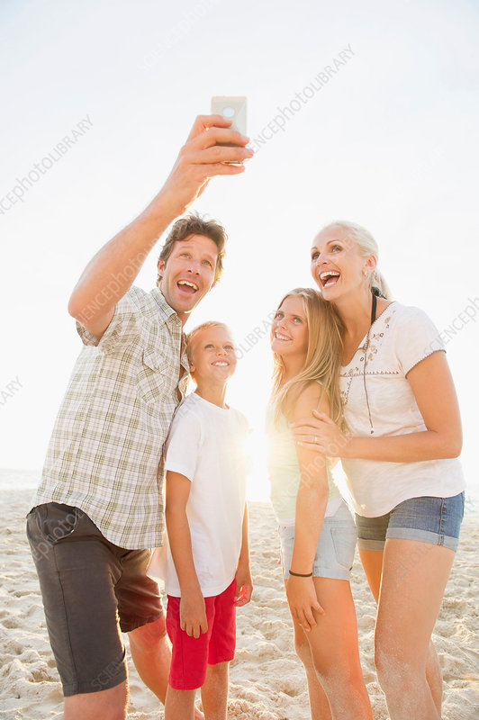 Family photographing themselves on beach