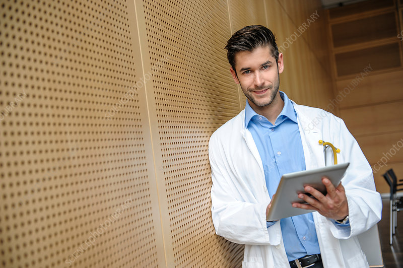 Young male doctor holding tablet