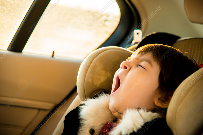 Young girl with yawning in car