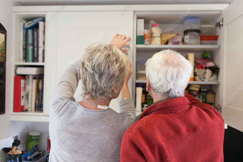 Senior couple checking kitchen cupboards