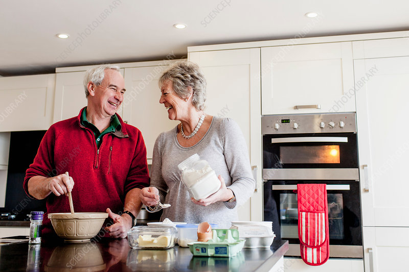 Senior couple baking together in kitchen