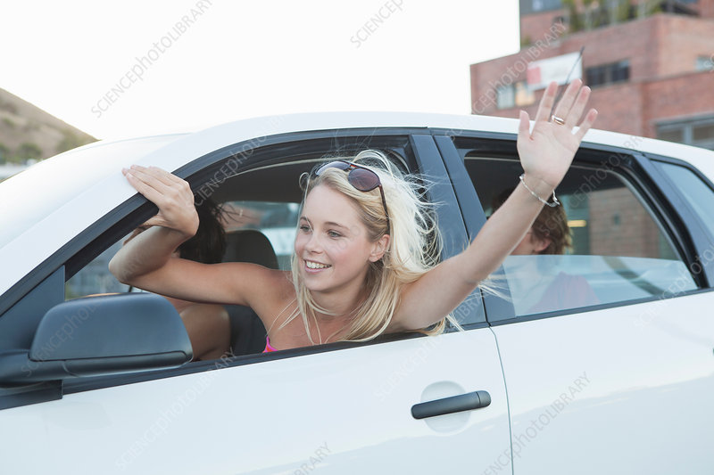 Woman waving through car window