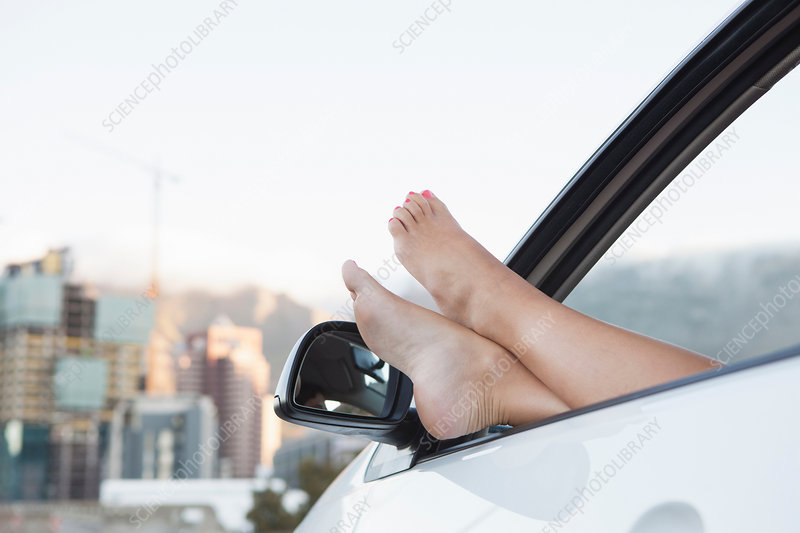Woman with feet up through car window