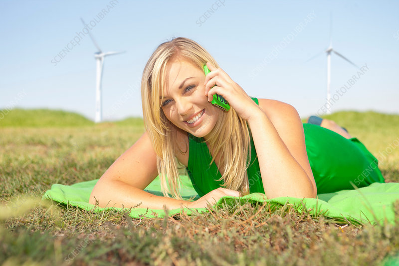Woman lying in field on green cell phone