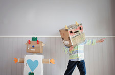 Boy with box covering head and toy robot