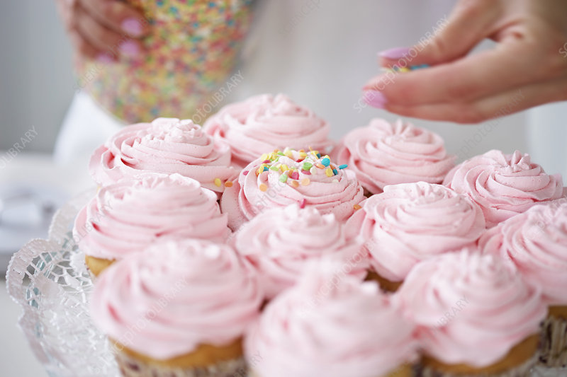 Woman decorating cupcakes