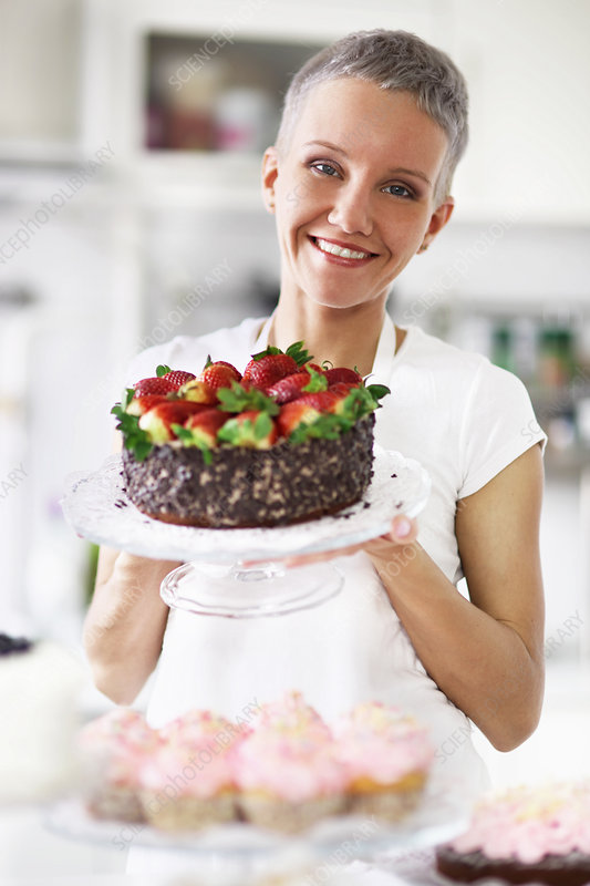 Woman holding cake with strawberries