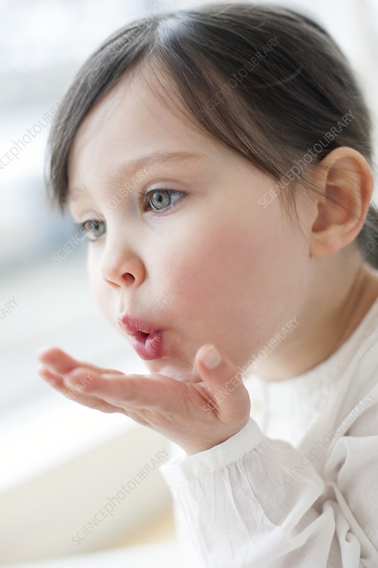 Three year old girl blowing a kiss