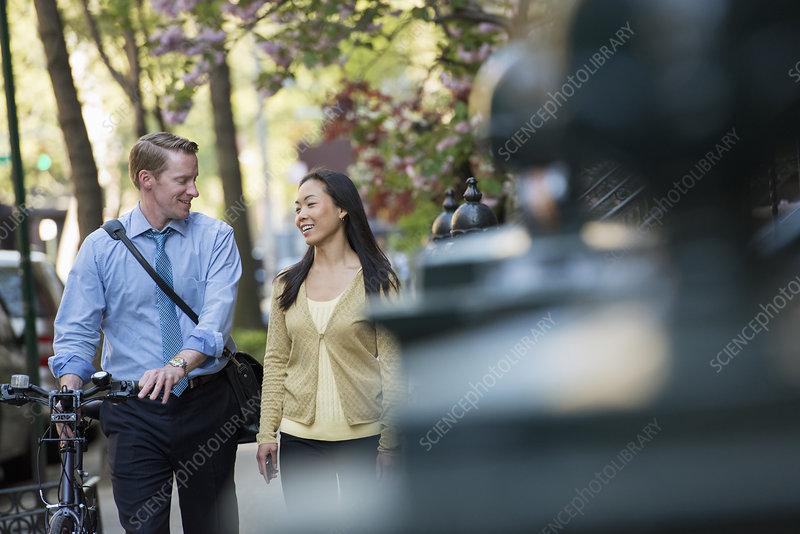 Couple, man pushing bicycle