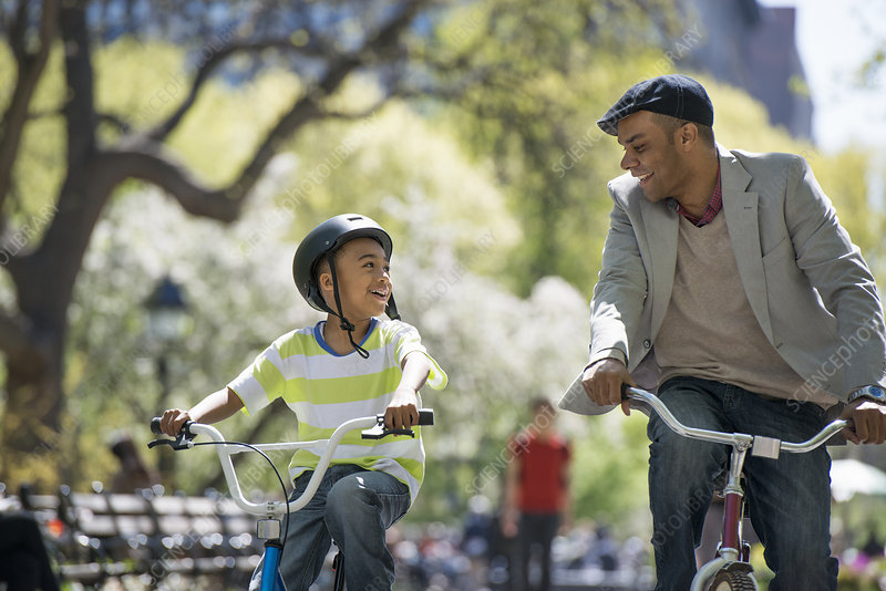 Father and son cycling in park