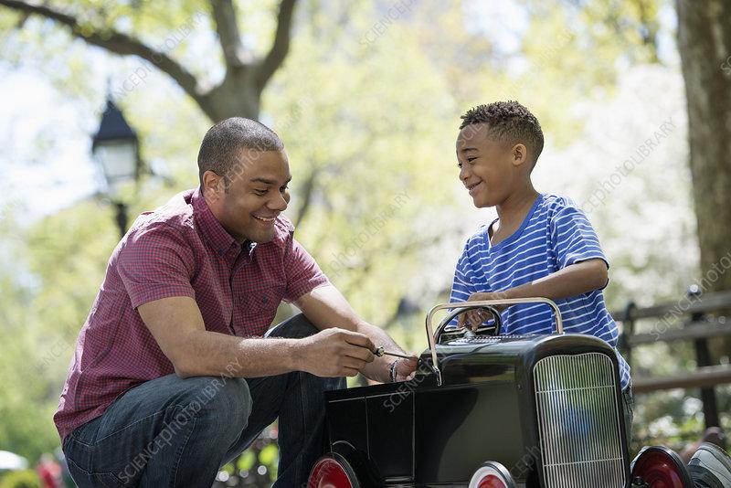 Boy riding an old fashioned peddle car