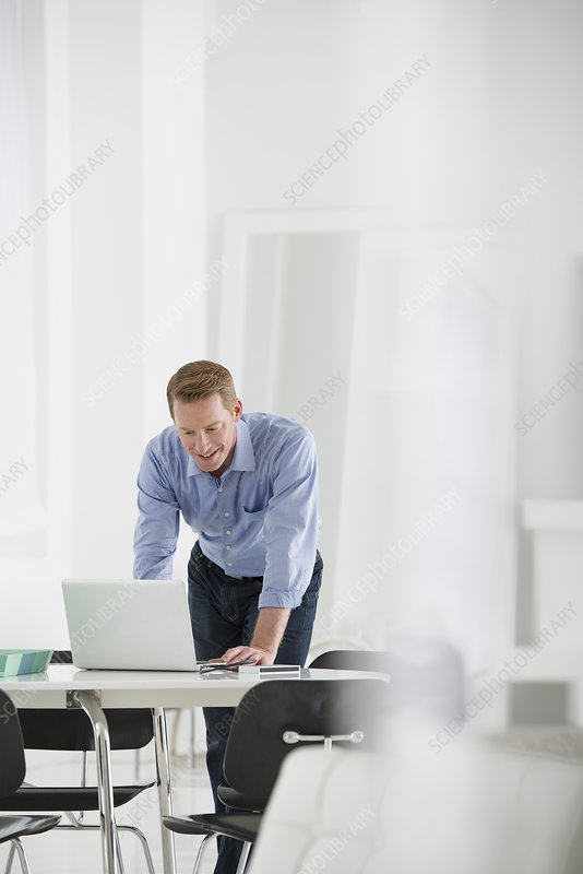 Businessman leaning down over Laptop
