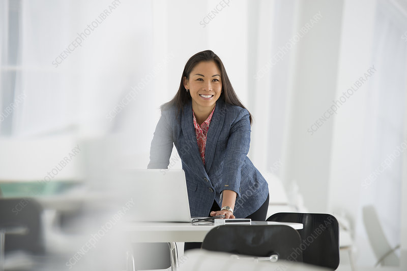 Businesswoman leaning over Laptop