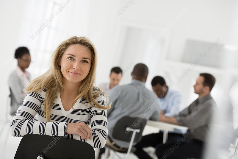 Woman seated separately from meeting