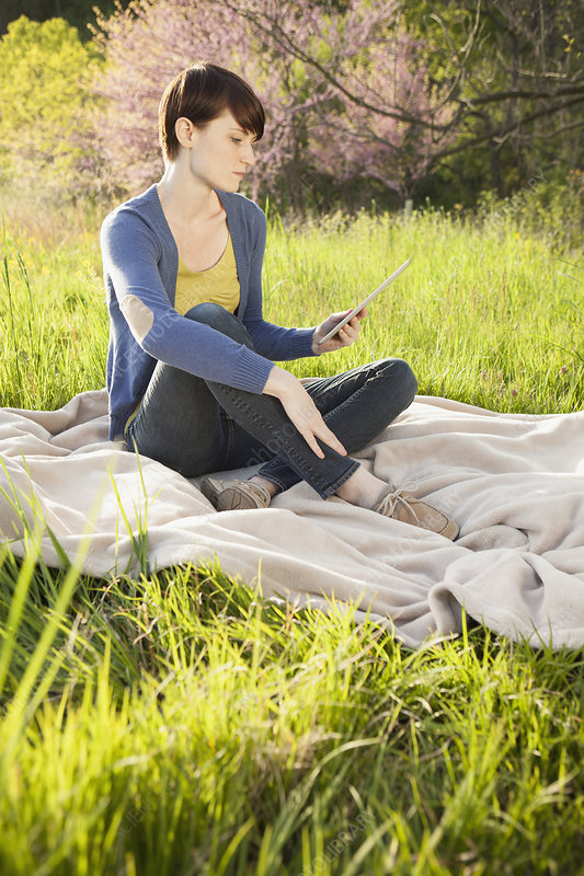 Woman using a digital tablet outdoors