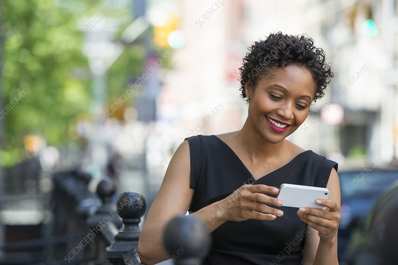 Woman on a street checking her phone