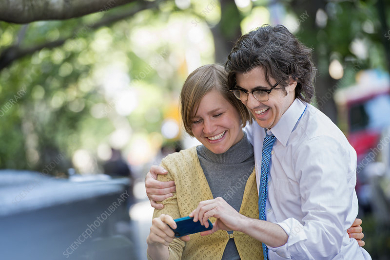 Two people checking a smart phone