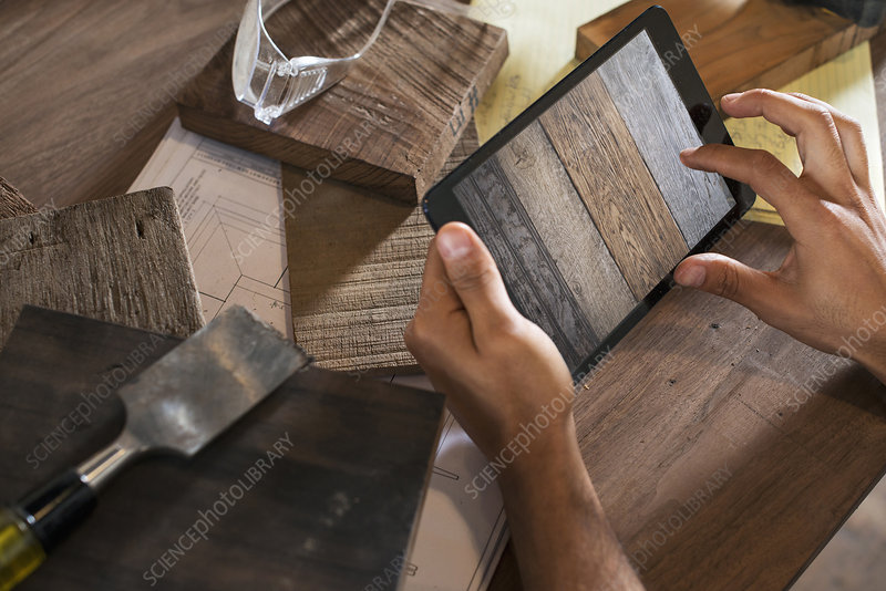 Man using tablet to photograph wood