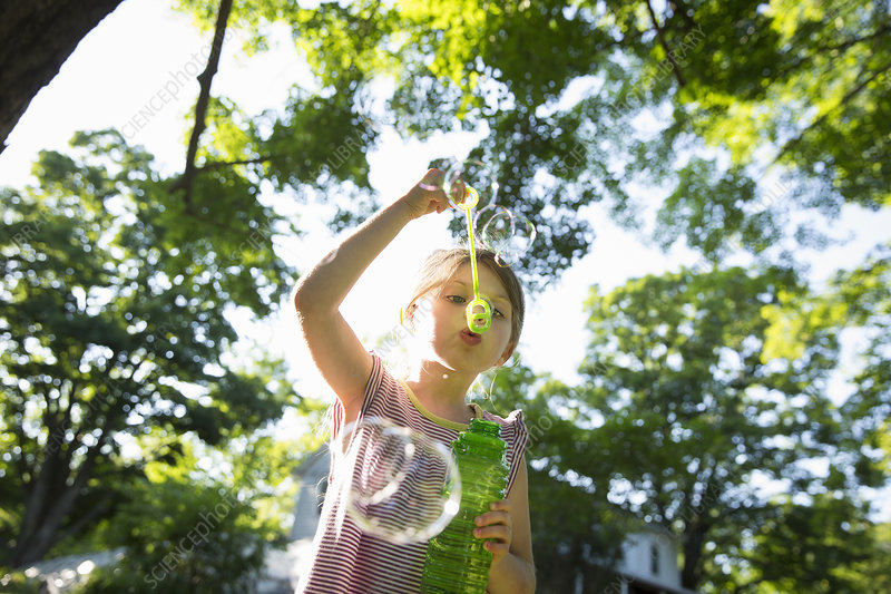 Girl blowing bubbles outdoors in summer