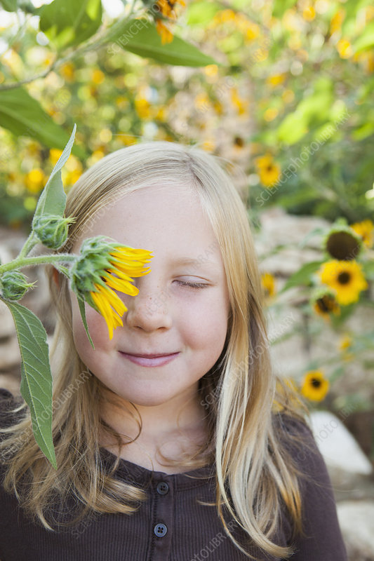 Girl with a sunflower over one eye