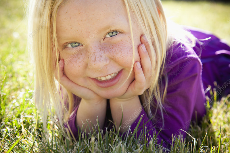 Child lying on the grass laughing