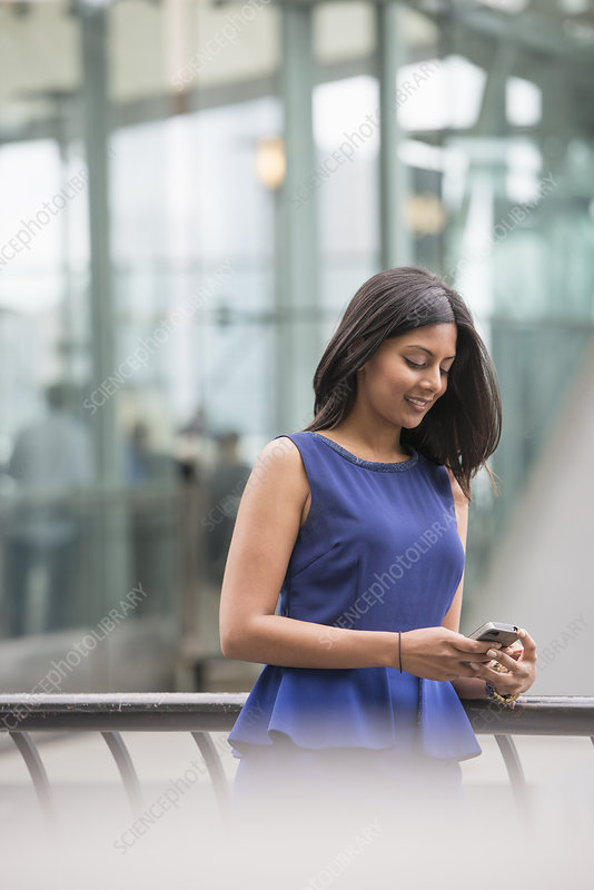 Woman in blue dress checking her phone